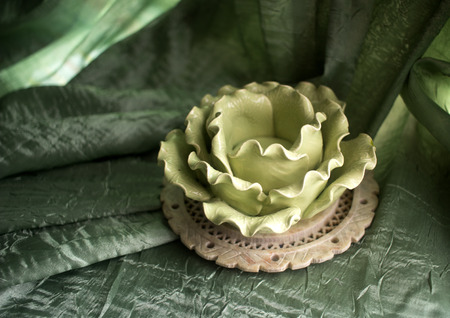 Candlestick against the background of green draperies with folds