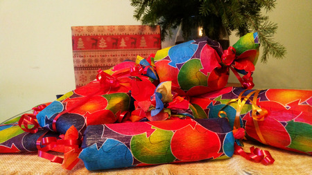 many gifts packed in colored paper and bandaged with ribbon