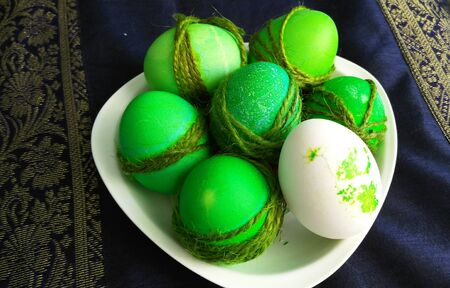 painted easter green eggs and one white on a plate Reklamní fotografie