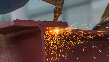 Metal Cutting With Acetylene Gas. Workman is working by use torch cut the iron in factory. Spark splash around the ground.