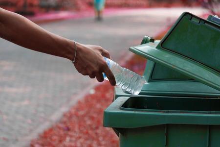 botes de basura: La mano que lanza botella en los botes de basura.