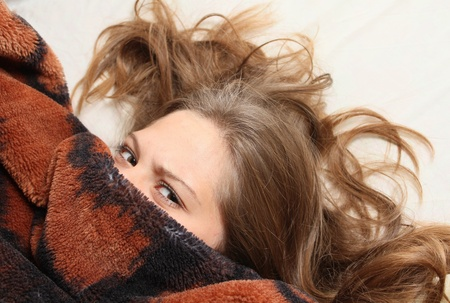 Young girl peeking out from under the blanket