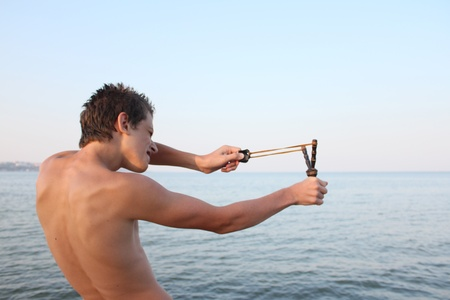 young boy shooting from a slingshot on the sea photo