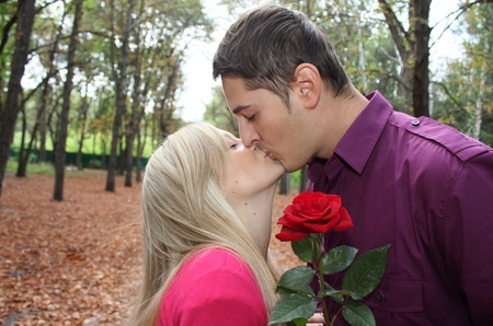 young boy kissing young beautiful girl with rose