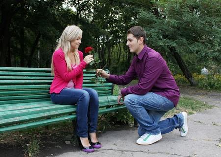 boy kneeling before girl and presenting rose Фото со стока