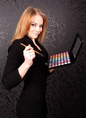 Woman with brush and multicolored eye shadows photo