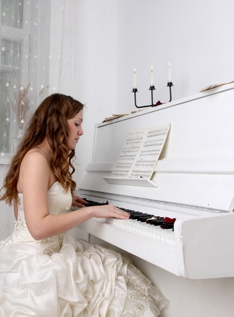 Woman in the white dress playing on the white piano photo