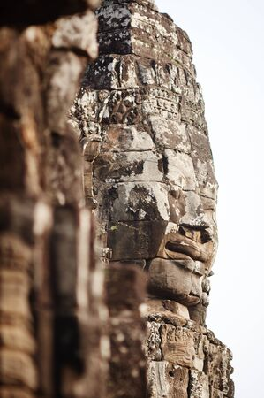 focus on the foreground: Stone Face in Bayon with soft focus foreground, Siem Reap Stock Photo