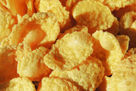 cowardly: A bunch of corn flakes cereal on a white background with milk. Breakfast