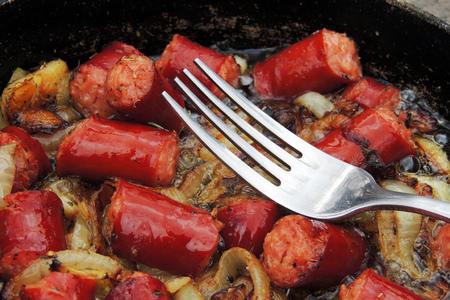 hairpiece: Fried sausage with onion in skillet. Stock Photo