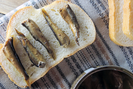 sprats: A tin of smoked sprats and bread. On sandwiches Stock Photo