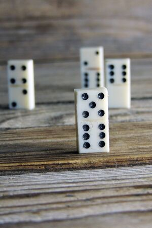 gambling stone: Domino. A bone on wooden background. Game. Stock Photo