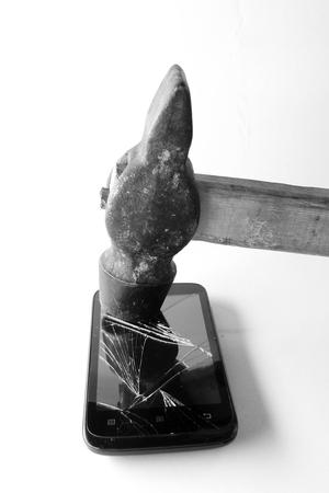 schermo del telefono rotto e martello su sfondo bianco