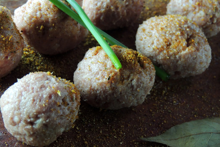 cooked pepper ball: Raw meatballs in bowl with ingredients on wooden background