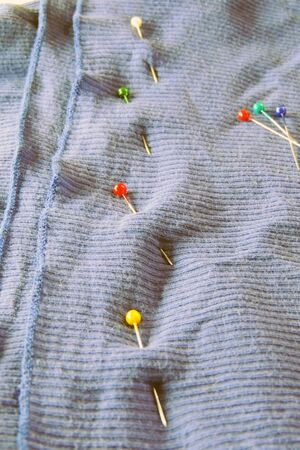 safety pin: blue denim clothing fragment with safety pin