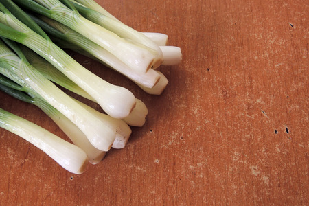 breadboard: Bunch of fresh green onions in bundle on breadboard table. Dark or neutral wooden background