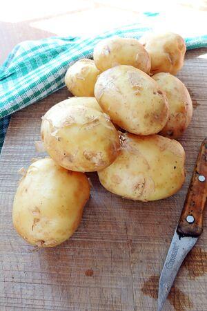 hardboard: Peeled raw potatoes and ceramic knife on hardboard. Top view. Isolated Stock Photo