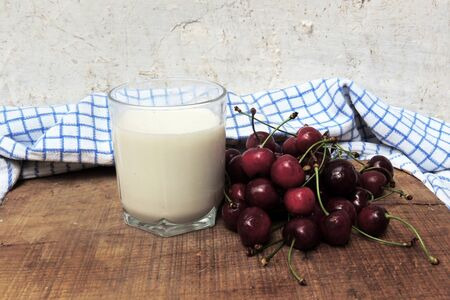 fruition: Red sweet cherries with water drops and glass of milk