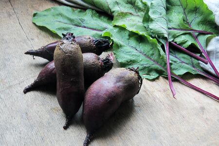 Young Beets on a wooden table and leaves