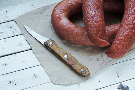 dry sausage: Sausage and knife on wooden background. Snack food