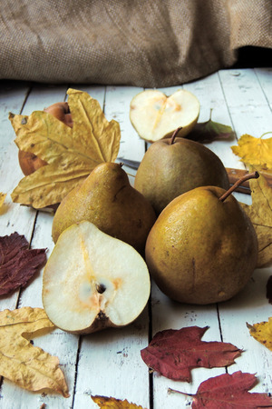 williams: Pear and autumn leaves on wood table closeup