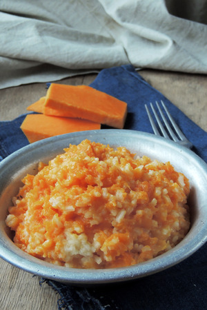 perle: Millet porridge with pumpkin in a clay bowl on a rustic wooden background