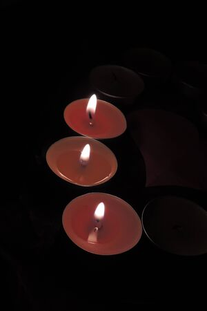 christian halloween: Small firing candles in catholic church on dark background. Filtered photo with effects