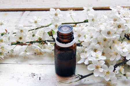 bath essence: Essential oil and spring flowers, on a white background