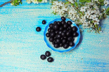 Peanuts in chocolate on the plate, blue background Stock Photo