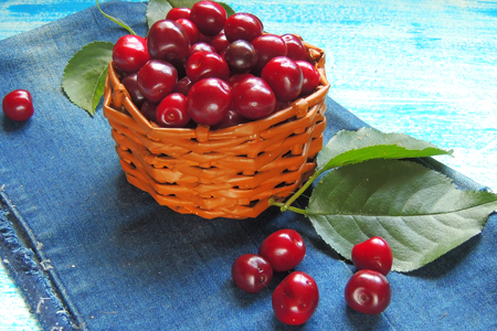 crannied: Ripe cherries in basket on old wooden table on countryside against summer foliage in sunlight Stock Photo