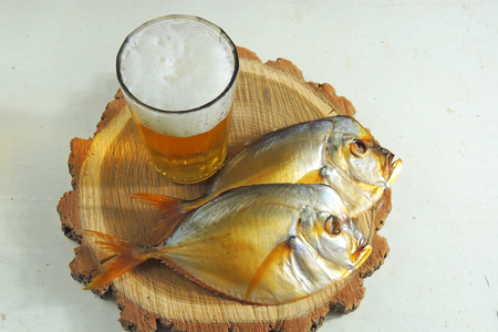 Two smoked Selene setapinnis, also known as Atlantic moonfish or Vomer setapinnis, on a white dish and the glass of lager beer on the old rustic table with fishing net 免版税图像