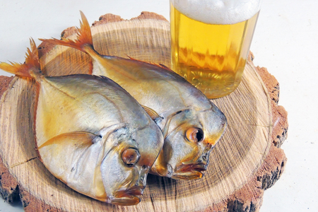 Two smoked Selene setapinnis, also known as Atlantic moonfish or Vomer setapinnis, on a white dish and the glass of lager beer on the old rustic table with fishing net Archivio Fotografico