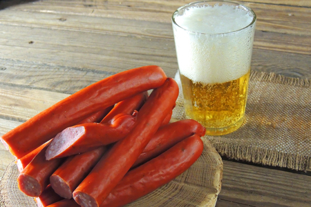 Traditional Oktoberfest menu. Beer being poured into a glass with foam, traditional snacks, sausages grilled. With green background Stok Fotoğraf