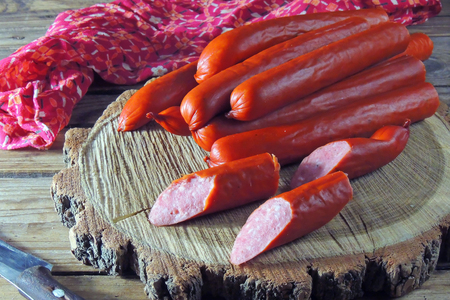 hunting sausages with vegetables and sauce on a cutting board on a dark background Standard-Bild - 116739559