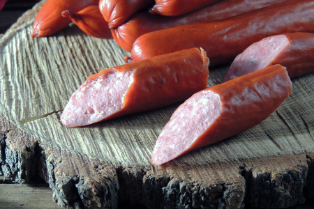 hunting sausages with vegetables and sauce on a cutting board on a dark background Standard-Bild - 116739565