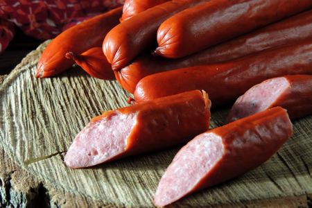 hunting sausages with vegetables and sauce on a cutting board on a dark background Standard-Bild - 116739564