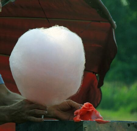 Hand rolling cotton candy in candy floss machine. Making candyfloss
