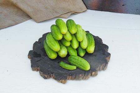 Cucumber on wooden plate and vintage background. Selective focus on cucumber
