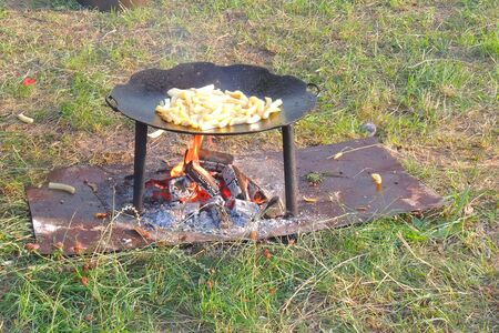 Cooking roasted French Fried potatoes for barbecue picnic. Fried bbq potatoes in a large frying pan on an open fire with smoke. Crispy Oven Baked French Fries at the stake