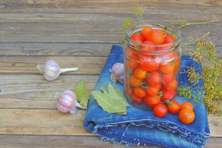 Jar with canned tomatoes and chili pepper on wooden table