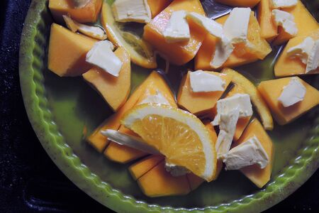 Pumpkin pieces and butter on the oven tray topped with sugar and spices ready to be baked 写真素材