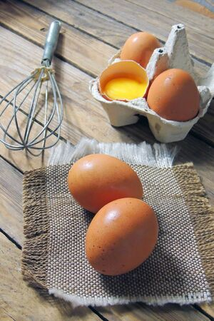 top view the eggs in black ceramic bowl and egg whisk put on wooden butcher 写真素材