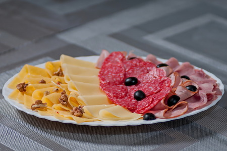chese: slices of cheese of sausage and black olives on a white dish