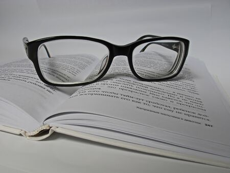 Glasses lie on a book on a white background photo