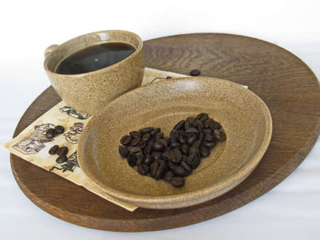 stylishness: cup of coffee with grains of coffee on a saucer and heart from coffee