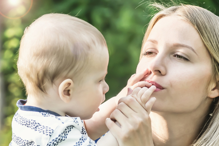 Pretty woman kissing the small fingers of her baby son Stock Photo