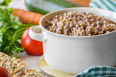 Natural organic food. Boiled buckwheat porridge in a pot. Fresh raw vegetables. Stock Photo