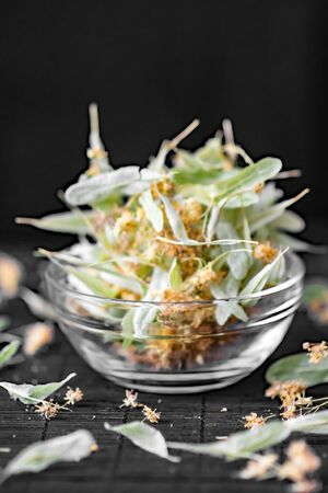 tilia cordata: Dried linden flowers and leaves In a transparent glass bowl on Black Background. Health Care Concept