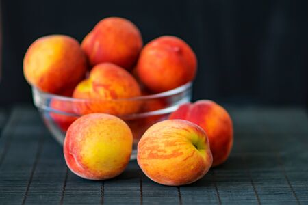 bakground: Ripe peaches in a transparent glass bowl on a black background. Summer fruits. Health Care Concept