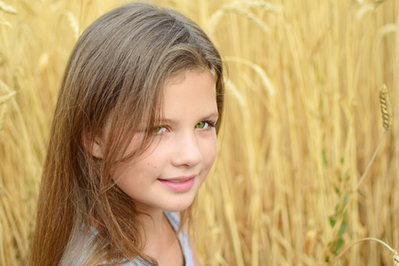 Close-up little girl with long hair green eyes in golden rye field summer day. Concept of purity, growth, happiness